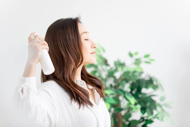 髪にスプレーする女性