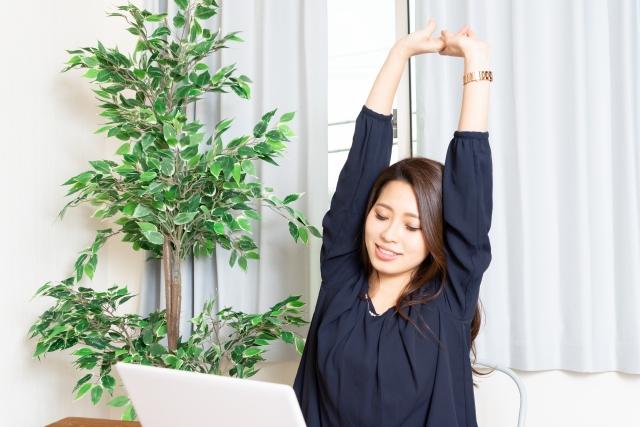 オフィスで伸びをする女性