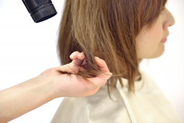 髪を乾かしてもらう女性